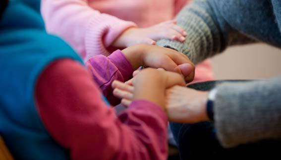 One child lays their hands over and grasps the hands of an adult. Another child rests their right hand on the adult's forearm. Only the arms and hands are visible in the photo