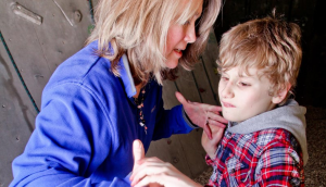 A woman in a purple jacket is face to face with a child wearing a checked shirt. The woman has her hands under the outspread hands of the child. She is using tactile signing